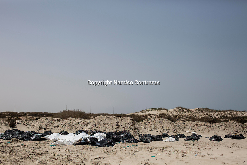 The bodies of dead migrants, collected from the Zawara shore by a vigilante group, are lined up for burial at an improvised graveyard in Abu Kammash, west Libya.