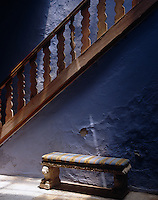 A carved stone bench with a striped silk seat is placed against the peeling paint of the staircase wall