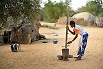 A woman grinds grain to feed her family in Timbuktu, a city in northern Mali which was seized by Islamist fighters in 2012 and then liberated by French and Malian soldiers in early 2013. She belongs to the Bella ethnic group, which has traditionally been exploited by Timbuktu's lighter-skinned groups.