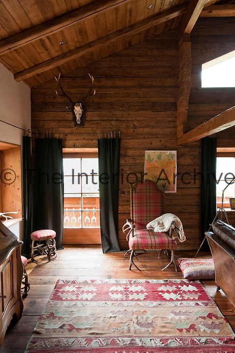A high back chair and a matching stool made from antlers and upholstered in a tartan fabric occupy a corner of the living room