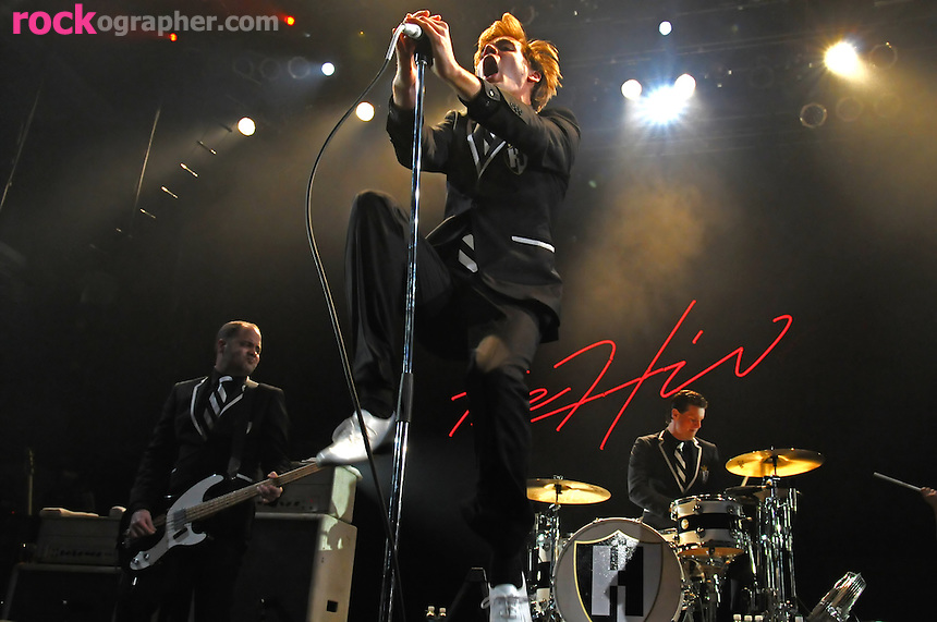 Singer Pelle Almqvist on stage with  Bassist Mattias Bernvall and drummer Christian Grahn at The Hives performance at Terminal 5 , NYC