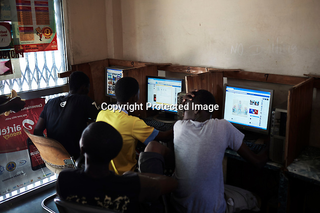 ACCRA, GHANA APRIL 17: Young men work on the computers in an Internet café on April 17, 2015 in Zongo Area in central Accra, Ghana. They work on Romance scams, credit card fraud and etc. The country is a center for different online scams. Both men and women are lured to send cash to someone they only met on the net.  Due to limited opportunities, many youngsters spend their days in Internet cafes trying to scam people form all over the world. (Photo by: Per-Anders Pettersson)