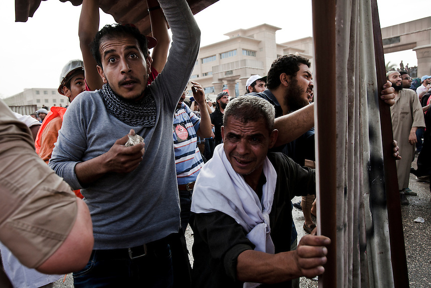 Protesters take cover behind a sheet of metal fencing during violent clashes between protesters and Military Police in front of the Egyptian Ministry of Defense in central Cairo's suburb of Abbaseya, March 4, 2012. Protesters marched on the MOD to demonstrate against over 20 deaths during a sit-in protest two days before. Photo: Ed Giles.