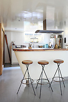 The basement kitchen has a contemporary bar which divides the cooking and eating areas