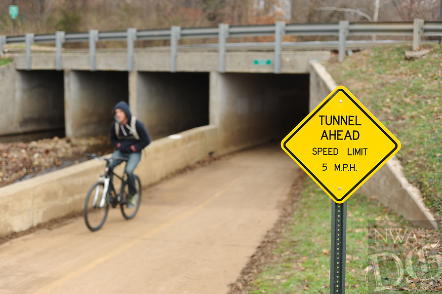 NWA Media/ANDY SHUPE - A cyclist utilizes the Scull Creek Trail, a section of the Northwest Arkansas Razorback Greenway, after passing beneath Appleby Road Sunday, Dec. 21, 2014, in Fayetteville. The greenway is a regional trail system that connects Northwest Arkansas.