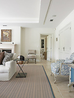 A modern rug in beige stripes covers the stone floor of the living room
