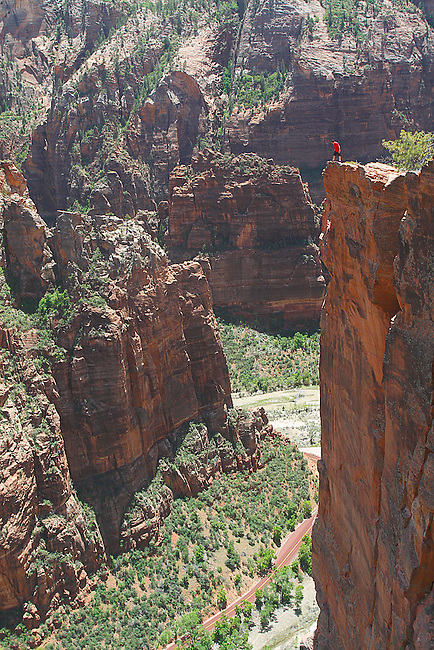 A BRAVE HIKER NEARS THE EDGE OF ZION CANYON AT ZION NATIONAL PARK