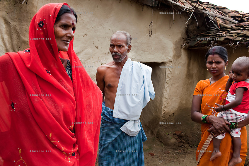 "(L-R)  Kelaji Adivasi (45), Tribhuvan Adivasi (50), Vinita (23, married when 14, has 3 children), and Vinita's baby stand in their house as Vinita visits the tribal hamlet. Tribhuvan, a farm labourer, says that ""it was a mistake to have so many children. Food is difficult for us."" Kelaji and Tribhuvan have a total of 6 children and live in poverty in Baul ka Dhera hamlet, Mugari Village, Allahabad, Uttar Pradesh, India. Allahabad, a poorer district of the state of Uttar Pradesh, is the most populated district of the most populous state of India. While Ghaziabad, located close to India's capital city, Delhi, has a population of 4,661,452 with a sex ratio of 878 girls against every 1000 boys, and a high literary percentage of 85%, Allahabad, has a population of 5,959,798 and a sex ratio of 902 girls against every 1000 boys and a literacy rate of 74.41%. Photo by Suzanne Lee / Panos London"