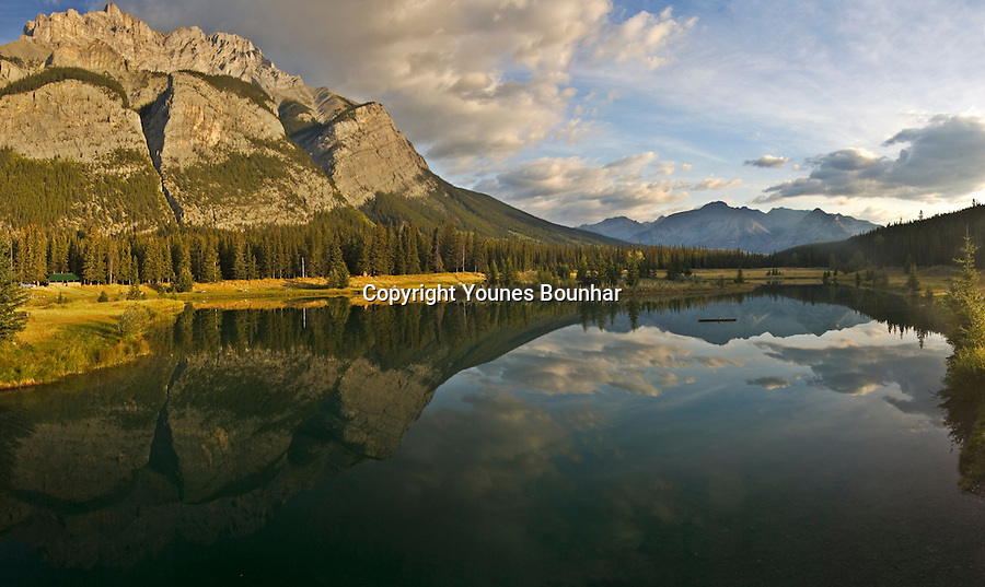 Cascade Mountain panorama with reflection in cascade ponds in the early morning. Beautiful clouds in the sky.