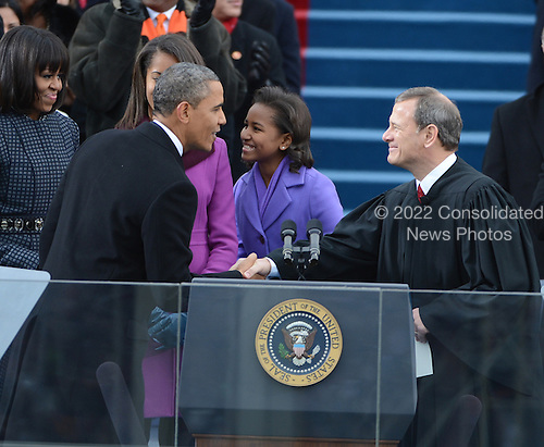 President Barack Obama shakes hands after being sworn-in for a second term as the President of the United States by Supreme Court Chief Justice John Roberts during his public inauguration ceremony at the U.S. Capitol Building in Washington, D.C. on January 21, 2013.  The first family looks on.    .Credit: Pat Benic / Pool via CNP