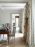 In the elegant family sitting room, neutral colours and natural materials abound. The abaca rug overlaying the parquet floor is by Patterson Flynn Martin and the curtains are a linen fabric by Chelsea Textiles. A simple writing desk and chair is set near a window.