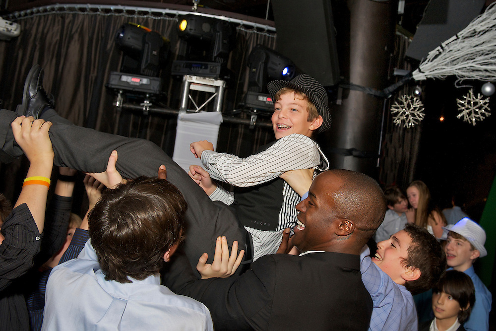 The Bar Mitzvah boy being lifted in the air during the horah.