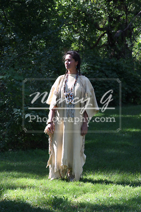 A Native American Indian Lakota Sioux woman standing in a leather dress