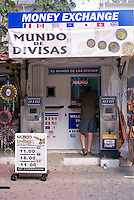 Young male tourist exchanging money at a booth in Playa del Carmen, Riviera Maya, Quintana Roo, Mexico.
