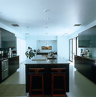A pair of retro stools stand at the end of the kitchen island in this large, contemporary kitchen