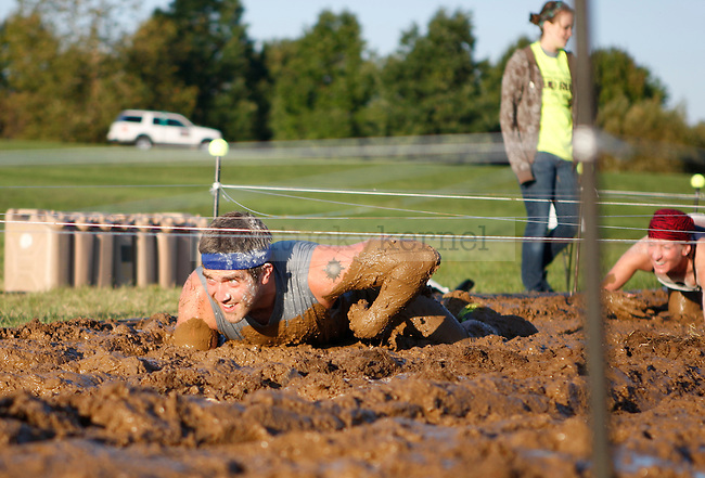 A participant climbs through the mud pit at the Mud Run near Commonwealth Stadium in Lexington, Ky., on Saturday, September 22, 2012. Photo by Tessa Lighty | Staff