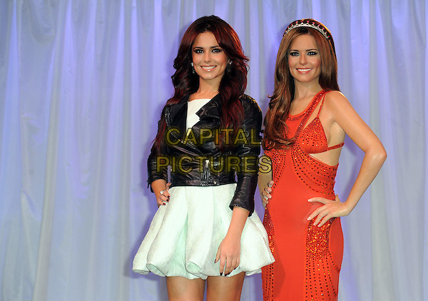 CHERYL COLE.Cheryl Cole and her new wax figure at Madame Tussauds, London, England. .October 20th, 2010 .waxwork half length white skirt dress black leather jacket  red sequins sequined tiara hairband alice band hand on hip.CAP/WIZ.© Wizard/Capital Pictures.