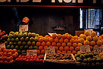 Asian man working behind a produce stall at the Pike Place Market with freah produce on display, downtown Seattle, Washington State USA
