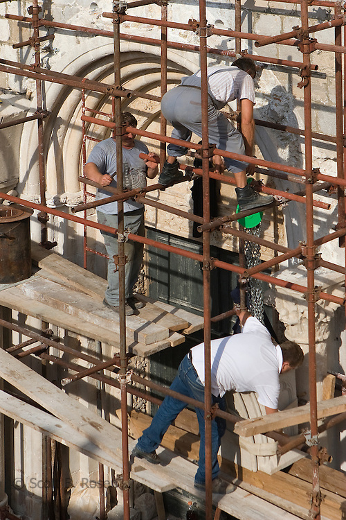 Croatian construction workers on scaffolding fixing the side of an 11th century builiding, Dubrovnik, Croatia