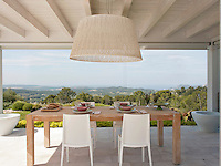 A covered, outside terrace provides the perfect place for alfresco dining. A Vibia lamp hangs above a bespoke table of bleached oak and white chairs, which stand on the paved area and give a fabulous view of the countryside beyond.