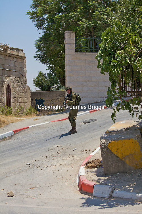 An Israeli soldier surveys the area after hearing children's voices during clashes with stone throwing Palestinian youths following a demonstration against Israel's controversial separation barrier in the West Bank town of Beit Jala near Bethlehem on 04/07/2010.