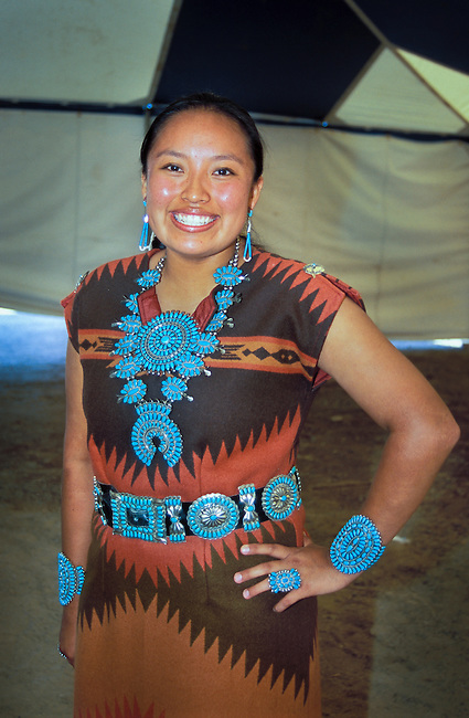 Navajo woman dressed in a woven wool dress adorned with traditional turquoise necklace, braclets, concho belt and ring attends the annual Shiprock festival in New Mexico