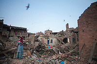 Nepali people stand on collapsed houses at Vaktapur, outskirt of Kathmandu, Nepal. May 1, 2015