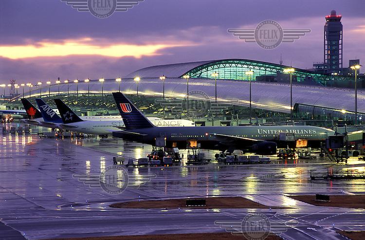 Jets lined up at Kansai Airport's main terminal building at sunset.