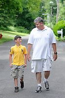 Jeffrey Gunn (right), a stay at home dad takes a walk with his son Colt Gunn (left), 11  Friday June 19, 2015 in Bensalem, Pennsylvania. For the past 15 years, Gunn has worked out of his home in his job with Meridian. (Photo by William Thomas Cain)