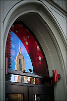 Empire State Building reflected in the Crimson night club's front door window.