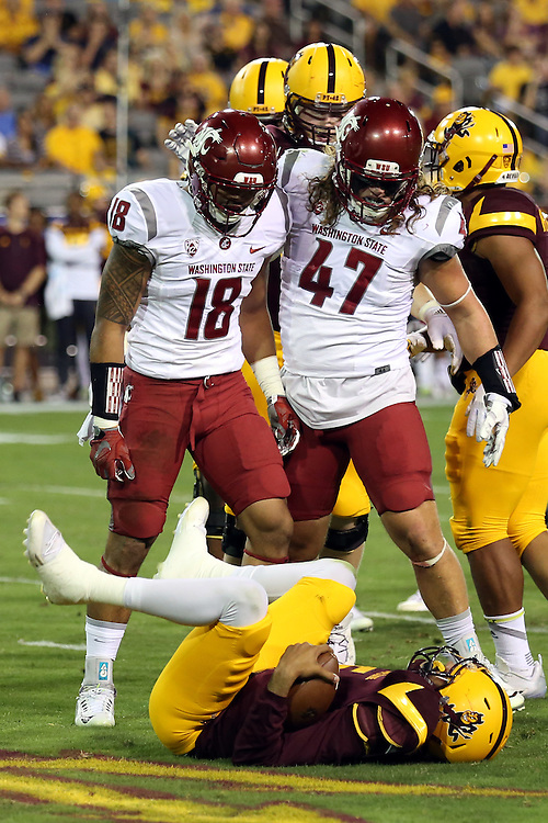 Shalom Luani (18), Washington State safety, and Peyton Pelluer (47), Washington State linebacker, stand over a team-tackled ASU ball carrier during the Cougars Pac-12 Conference victory over the UCLA Bruins, 27-21, on October 15, 2016, at Martin Stadium in Pullman, Washington.