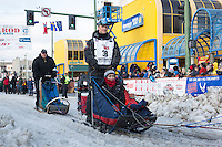 Charley Bejna and team leave the ceremonial start line with an Iditarider at 4th Avenue and D street in downtown Anchorage, Alaska during the 2015 Iditarod race. Photo by Jim Kohl/IditarodPhotos.com