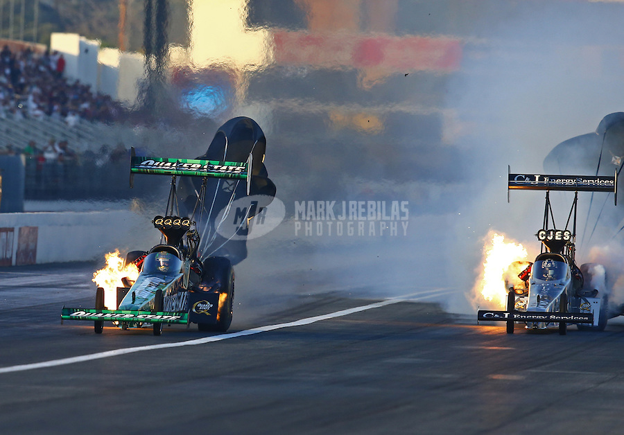Feb 12, 2016; Pomona, CA, USA; NHRA top fuel driver Leah Pritchett (left) on fire alongside teammate Dave Connolly during qualifying for the Winternationals at Auto Club Raceway at Pomona. Mandatory Credit: Mark J. Rebilas-USA TODAY Sports