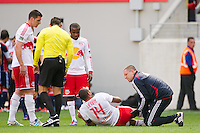 A trainer examines the hamstring of Thierry Henry (14) of the New York Red Bulls during the first half against the New England Revolution during a Major League Soccer (MLS) match at Red Bull Arena in Harrison, NJ, on April 28, 2012.