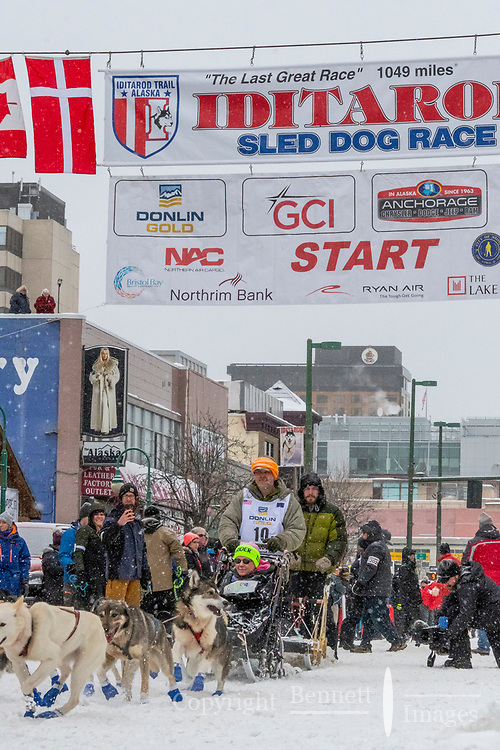 Lev Shvarts  and team leave the ceremonial start line with an Iditarider and handler at 4th Avenue and D street in downtown Anchorage, Alaska on Saturday March 7th during the 2020 Iditarod race. Photo copyright by Cathy Hart Photography.com