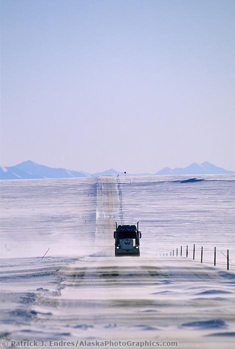 Semi truck, high winds blow drifting snow across the James Dalton Highway north of the Brooks Mountain Range, on Alaska's Arctic Coastal Plains.