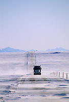 Semi truck, high winds blow drifting snow across the James Dalton Highway north of the Brooks Mountain Range, on Alaska's Arctic Coastal Plains.