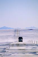 Semi truck, high winds blow drifting snow across the James Dalton Highway north of the Brooks Range, on Alaska's Arctic coastal plains.
