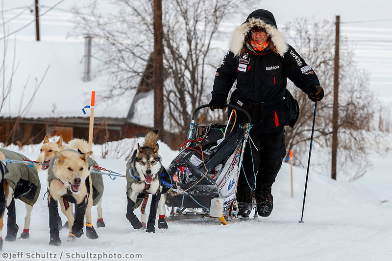 Allen Moore runs up the hill into the Ruby checkpoint during the 2017 Iditarod on Thursday morning March 9, 2017.<br /> <br /> Photo by Jeff Schultz/SchultzPhoto.com  (C) 2017  ALL RIGHTS RESERVED