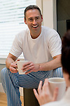 Mature man holding coffee cup, conversing with his mate