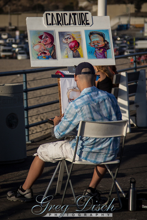 A artist drawing caricatures on The Santa Monica Pier. The Pier is  located at the foot of Colorado Avenue in Santa Monica, California and is a prominent, 100-year-old landmark. The pier contains Pacific Park, a family amusement park with a large Ferris wheel.<br /> <br /> the current Santa Monica Pier is actually two adjoining piers that long had separate owners. The long, narrow Municipal Pier opened September 9, 1909, primarily to carry sewer pipes beyond the breakers, and had no amenities. The short, wide adjoining Pleasure Pier to the south, a.k.a. Newcomb Pier, was built in 1916 by Charles I. D. Looff and his son Arthur, amusement park pioneers.