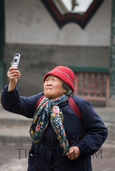Woman takes a photograph with a mobile phone at The Summer Palace, Beijing, China