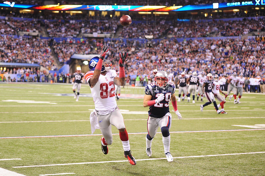 Feb 5, 2012; Indianapolis, IN, USA; New York Giants wide receiver Mario Manningham (82) makes a catch in front of New England Patriots free safety Sterling Moore (29) during the second half of Super Bowl XLVI at Lucas Oil Stadium.  Mandatory Credit: Mark J. Rebilas-
