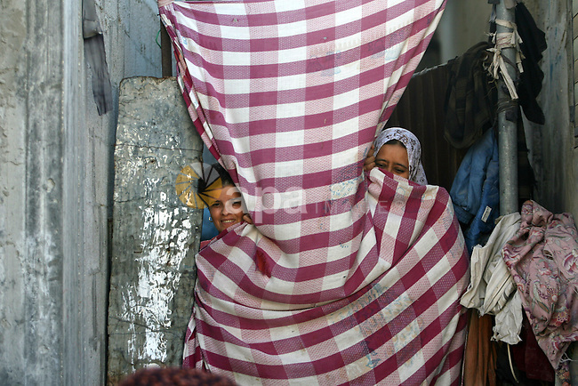 Palestinian women look through a curtain in front of their home in Rafah refugee camp, southern Gaza Strip, during Muslims fasting month of Ramadan, July 29, 2013. Ramadan is the holiest month in the Muslim calendar, during which people refrain from eating, drinking and smoking from sunrise to sunset. Photo by Eyad Al Baba