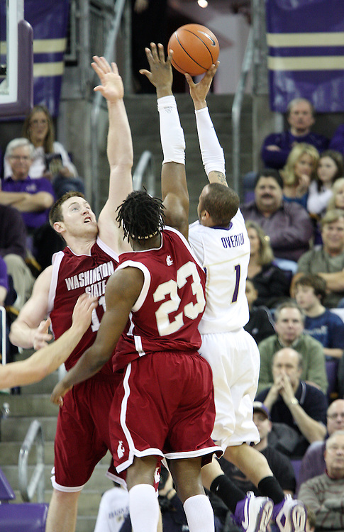 Aron Baynes (#11) and DeAngelo Casto (#23) of Washington State attempt to block the shot of Venoy Overton (#1) during the Cougars Pac-10 conference showdown with the University of Washington on March 7, 2009, in Seattle, Washington.  Both teams came in to the game on a roll, and in a hard fought battle, the Huskies prevailed 67-60 to wrap up the regular season Pac-10 championship.