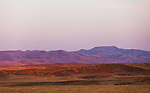 The hills of Southeast Oregon are bathed in a purple glow as the sun sets below the horizon on a warm summer day.