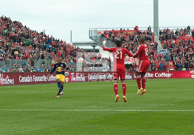 Toronto, Ontario - May 17, 2014: New York Red Bulls forward Thierry Henry #14 attempts a free kick as Toronto FC forward Jermain Defoe #18 and Toronto FC midfielder Jonathan Osorio #21 try to defend during the second half in a game between the New York Red Bulls and Toronto FC at BMO Field. Toronto FC won 2-0.