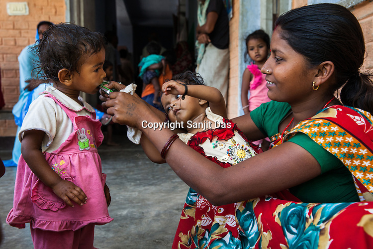 21 year old Asha Devi feeds RUTF to a neighbour's daughter at the government health centre in  Hanuman Nagar, Saptari, Nepal.