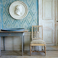 A plaster medallion on blue and white French Directoire wallpaper