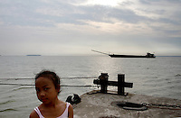 A young girl and a sand-ship at Dongting Lake, Hunan Province. Dongting Lake has decreased in size in recent decades as a result of land reclamation and damming of the Yangtze. China. 2010